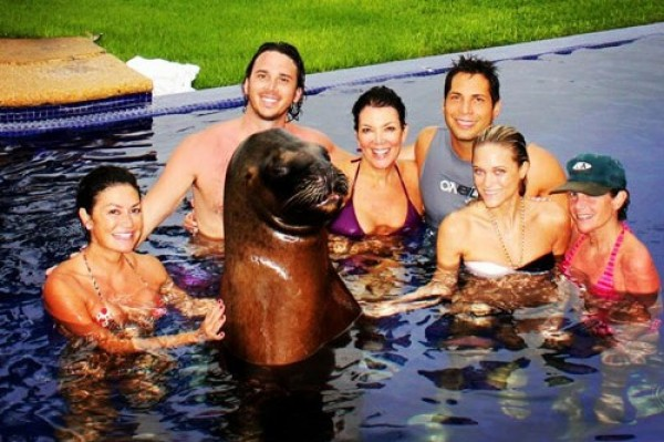 Kris Jenner surrounded by shirtless men, a seal and Joe Francis (The GIRLS GONE WILD King